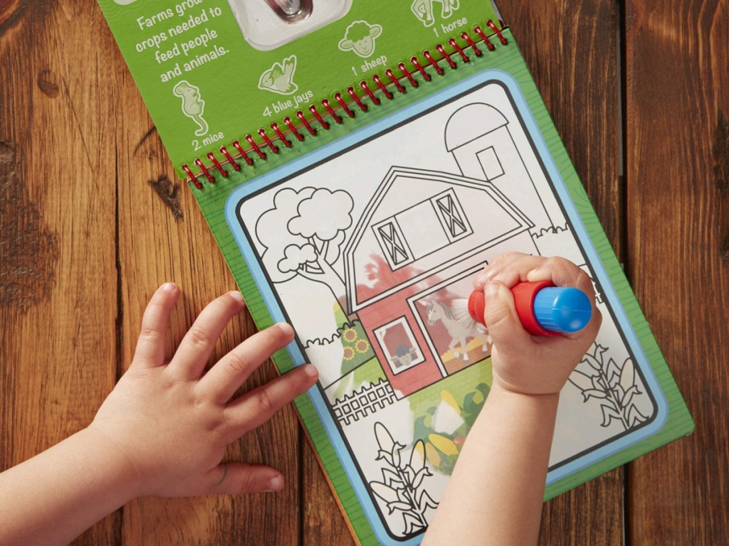 small child's hand doing a melissa and doug water wow farm book