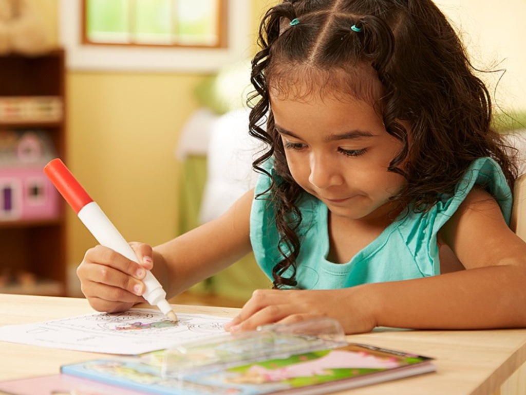 little girl sitting at a table coloring in a melissa and doug activity book
