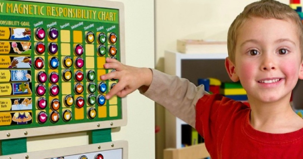 little boy pointing to a melissa and doug responsibility chart
