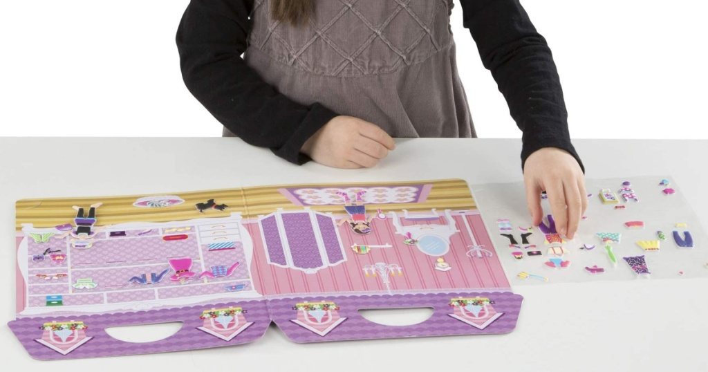 little girl playing with melissa and doug puffy sticker set