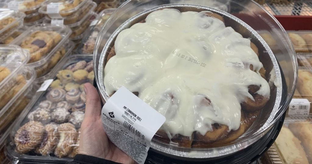 hand holding a tray of cinnamon rolls
