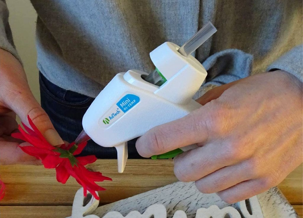 person using a hot glue gun on a fake flower