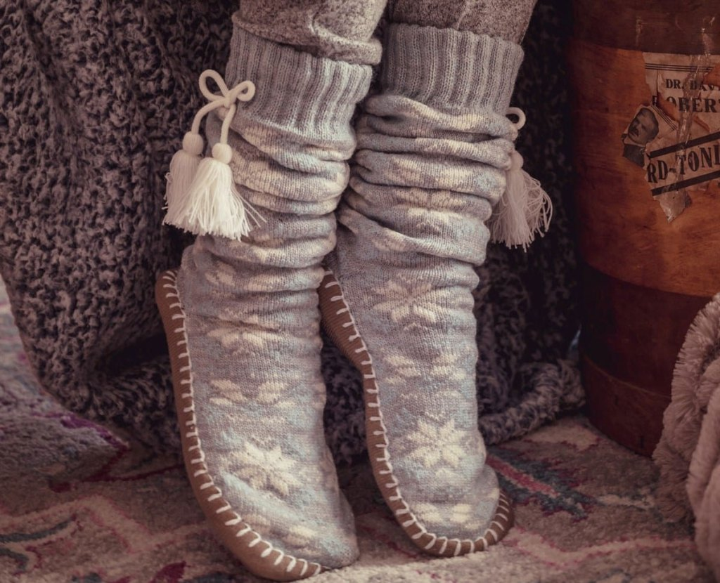 person wearing grey pair of muk luks slipper socks