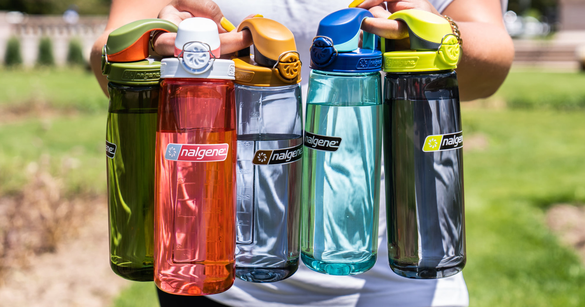 woman holding five different colored water bottles outside