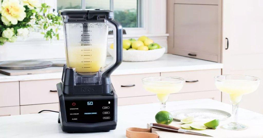 ninja blender on kitchen counter blending up margaritas