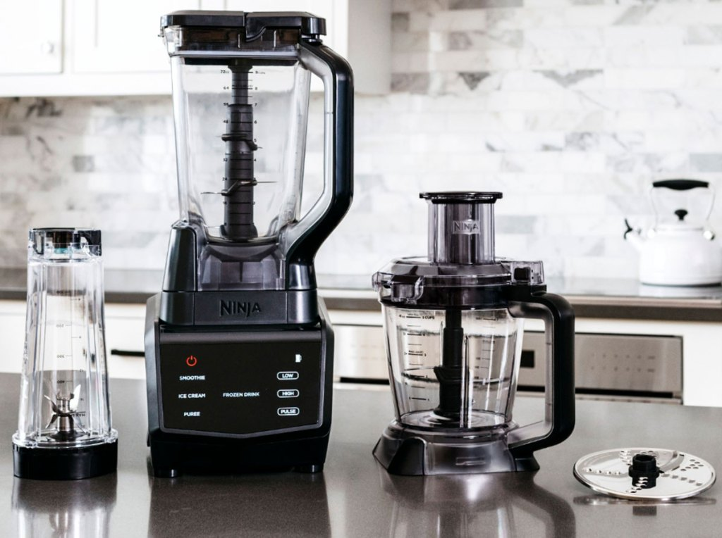 ninja blender on kitchen counter with single serve cup, food processor attachment, and blade