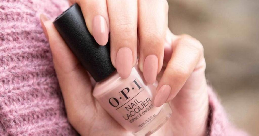 hand holding OPI nail polish pink