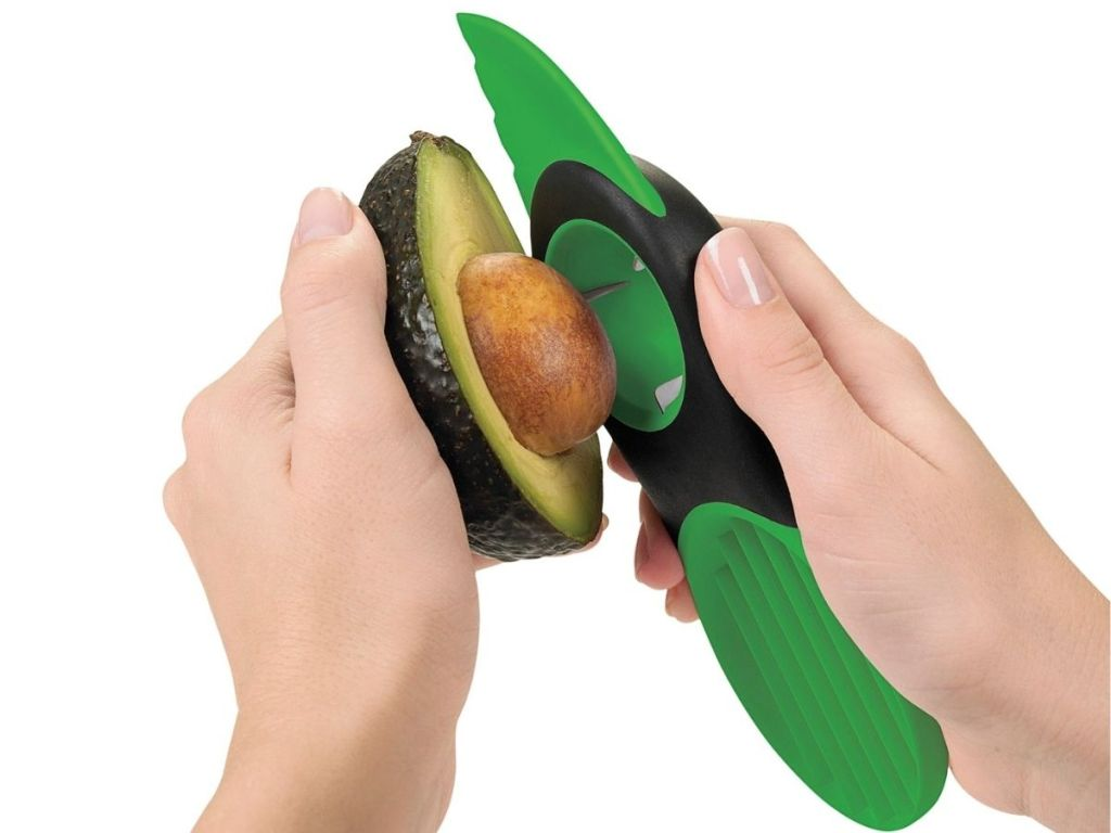 hands using OXO Avocado Slicer