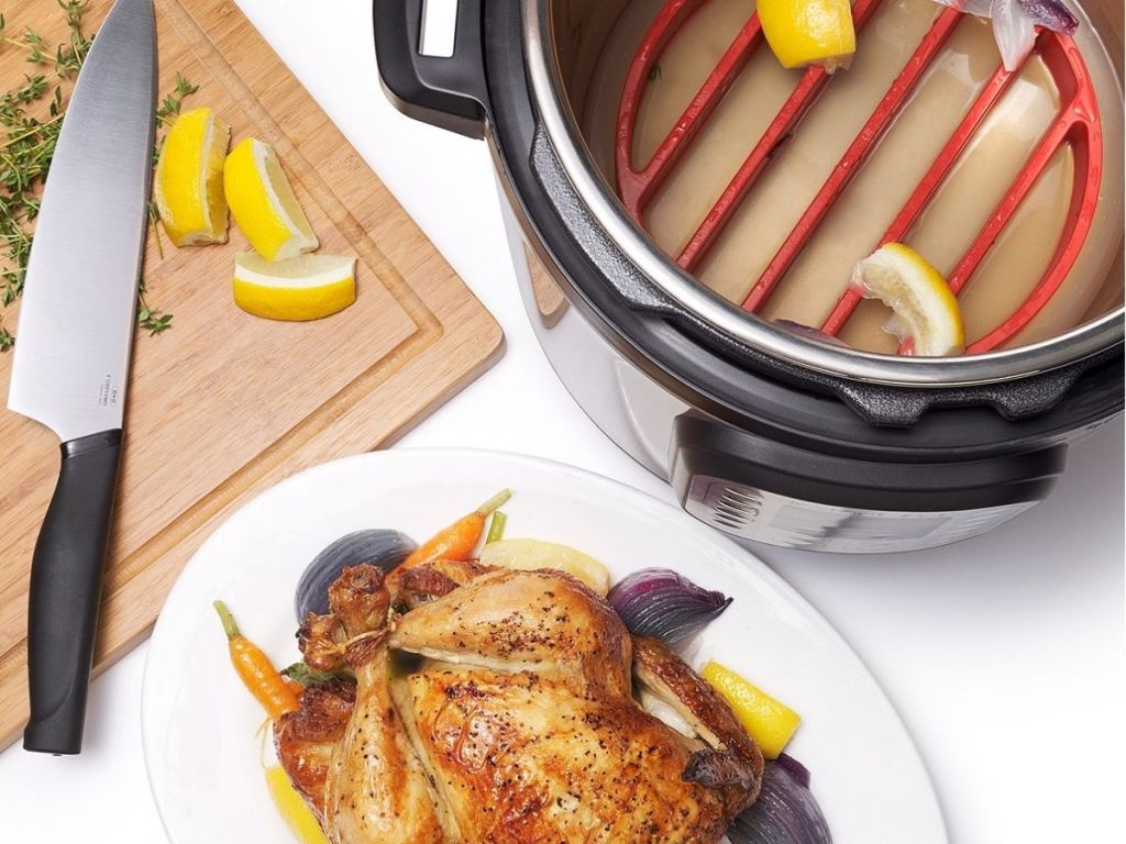 Cooked chicken next to pressure cooker
