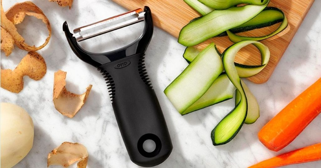 OXO Y Peeler laying with veggies and a cutting board
