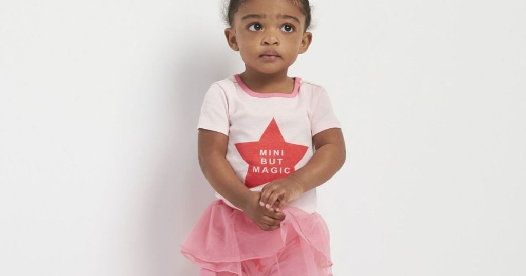little girl wearing a pink shirt and tutu