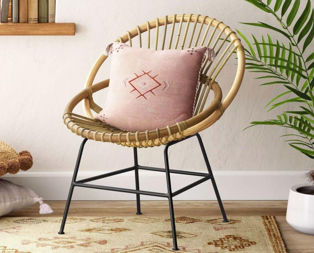 rattan papasan chair with pink throw pillow