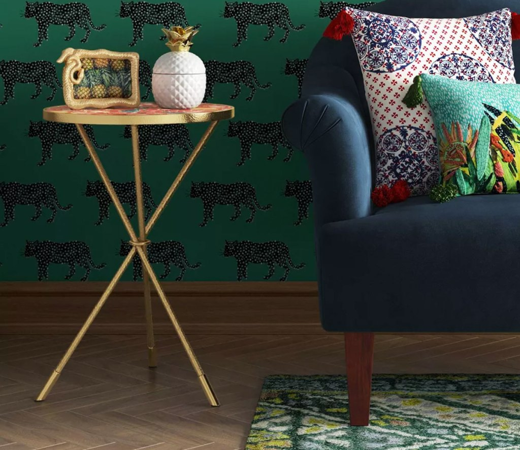 round accent table with gold legs next to blue couch