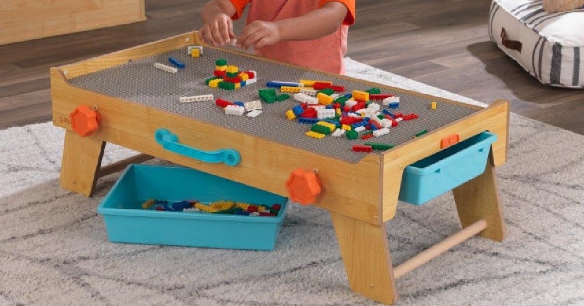 child sitting behind a kidkraft activity table