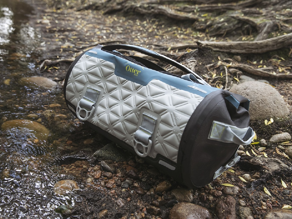 gray, blue, and black dry duffle on ground in woods