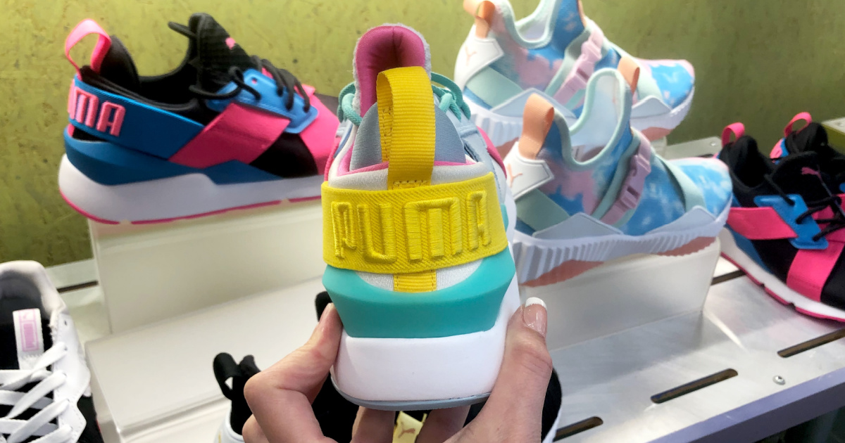 Hand holding kids PUMA brand shoes in-store