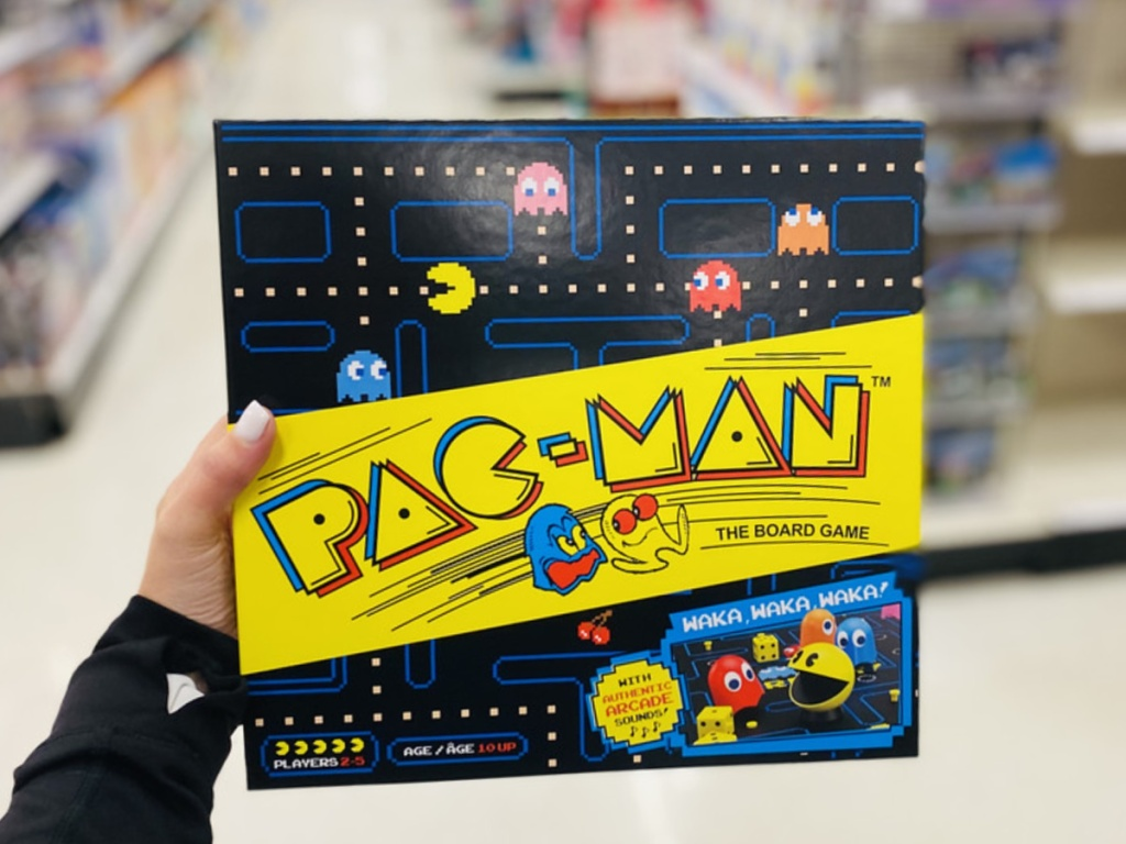 woman's hand holding Pac-Man board game in store