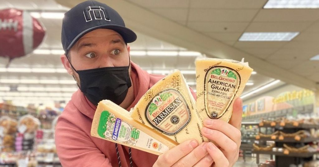 man holding three wedges of Parmesan Cheese at the store and looking scared of it