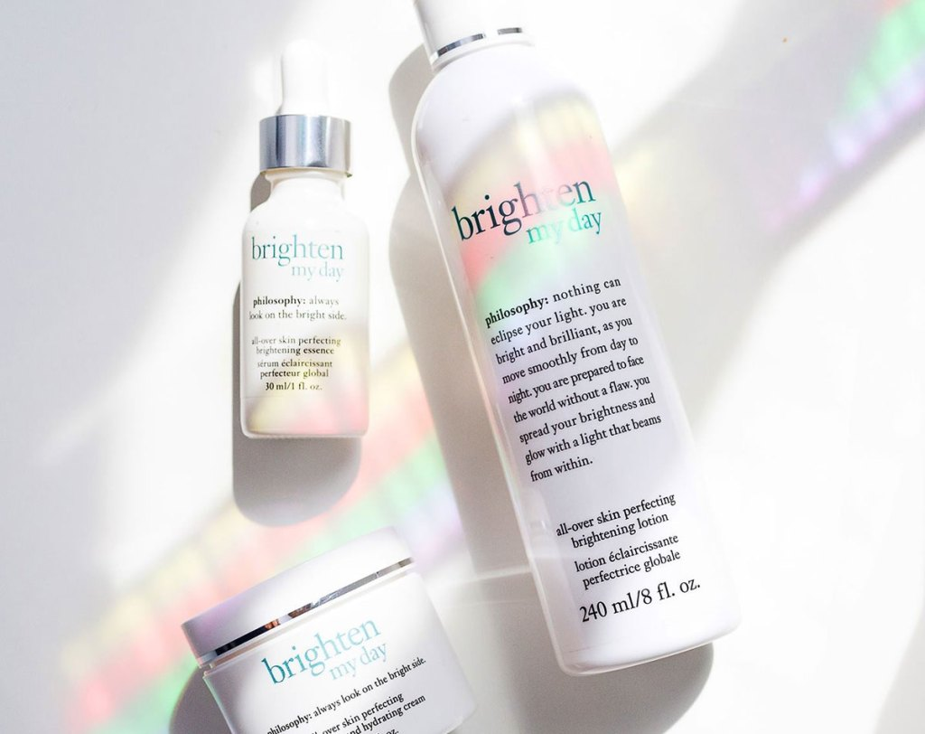 three white bottles of facial products with rainbow shining on them