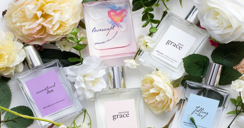 bottles of philosophy fragrances surrounded by flowers