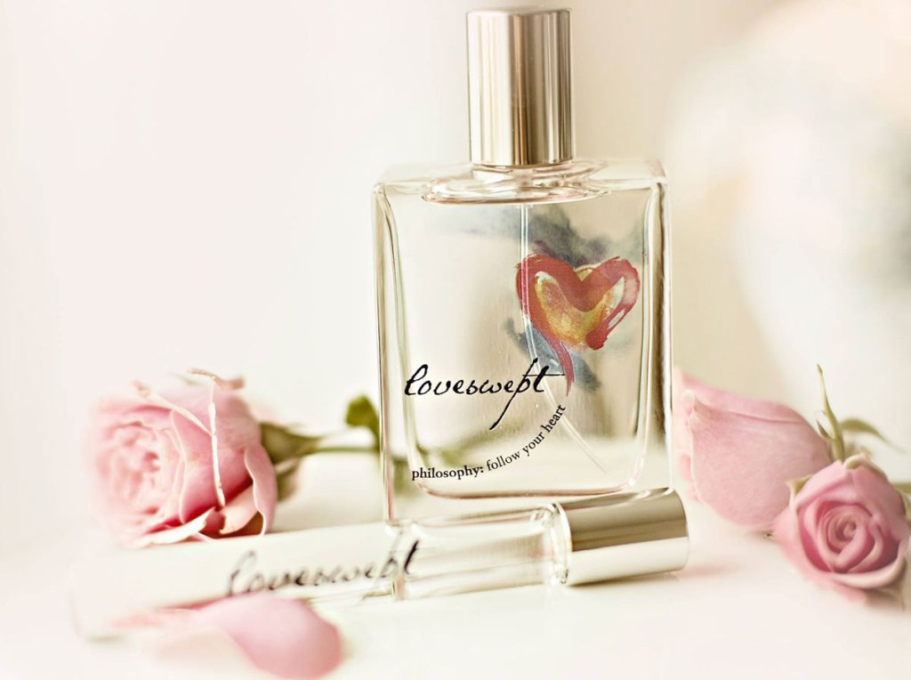 loveswept perfume with pink roses around it