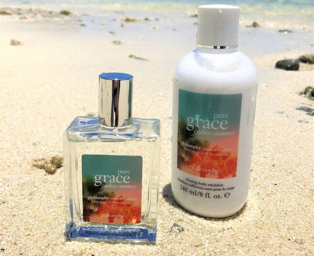philosophy perfume and body lotion bottles in sand at beach