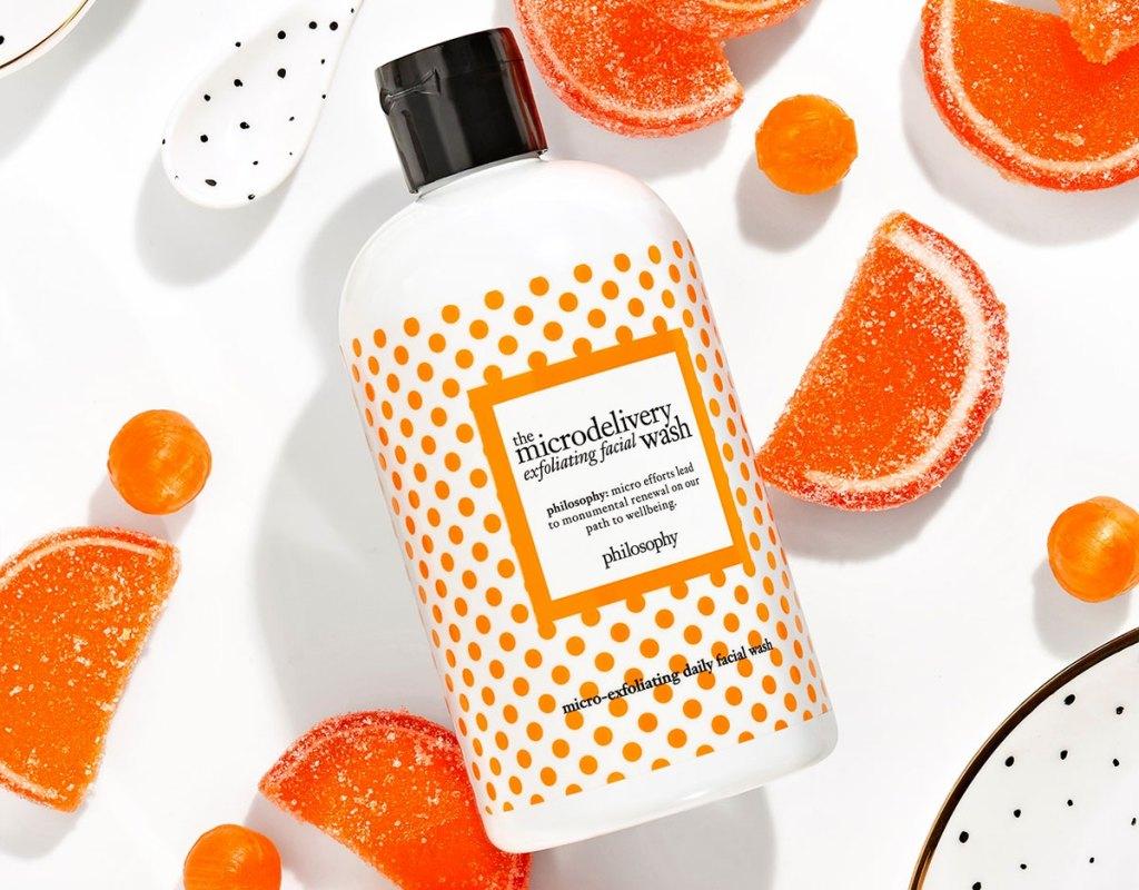 white and orange bottle of face wash with candy orange slices around it