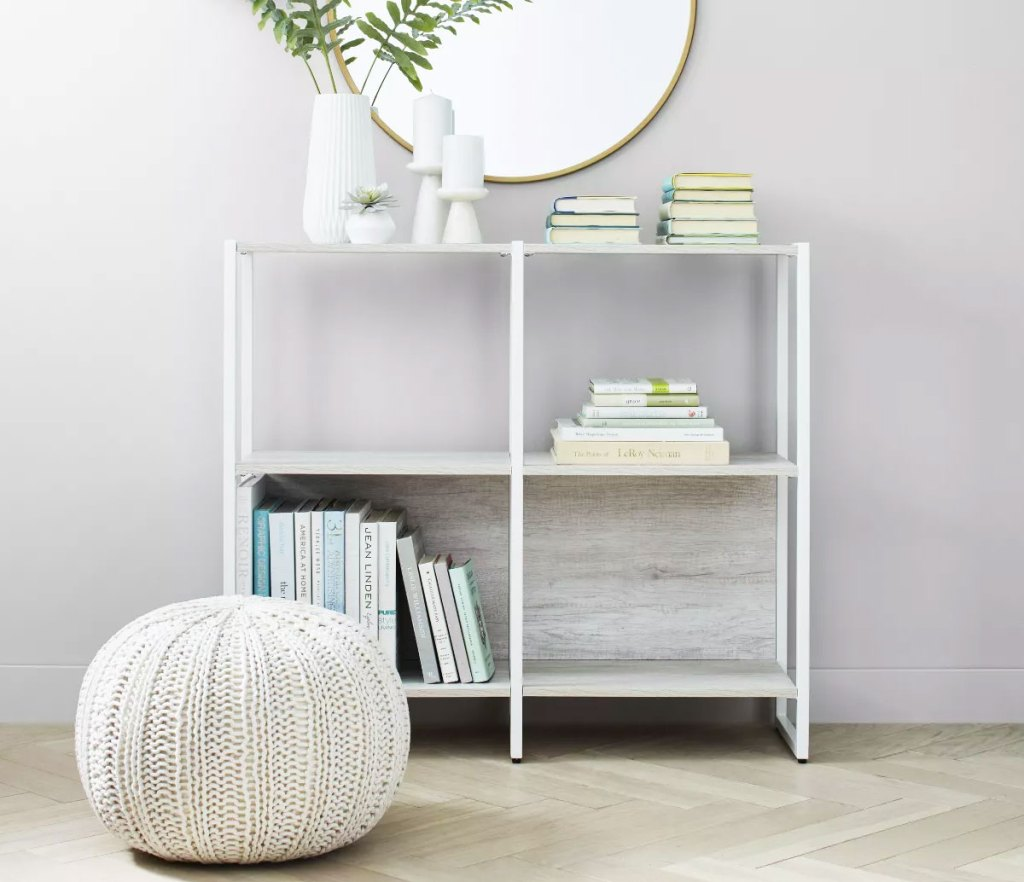 cubby bookcase with round mirror above it