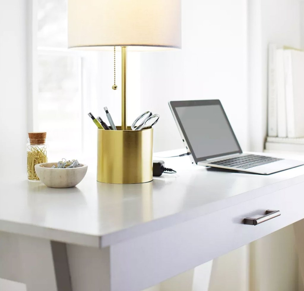 white desk with lamp and laptop on it