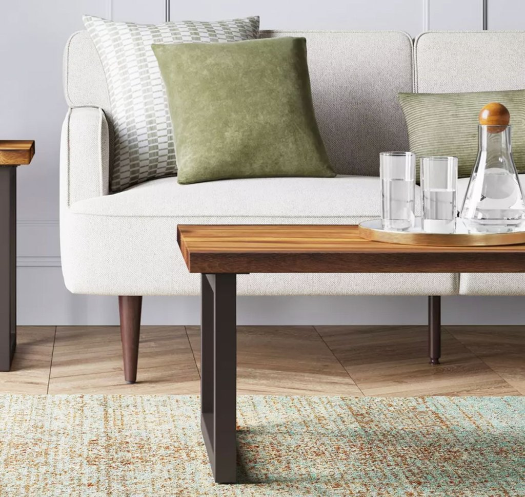 wood top coffee table in front of a white couch