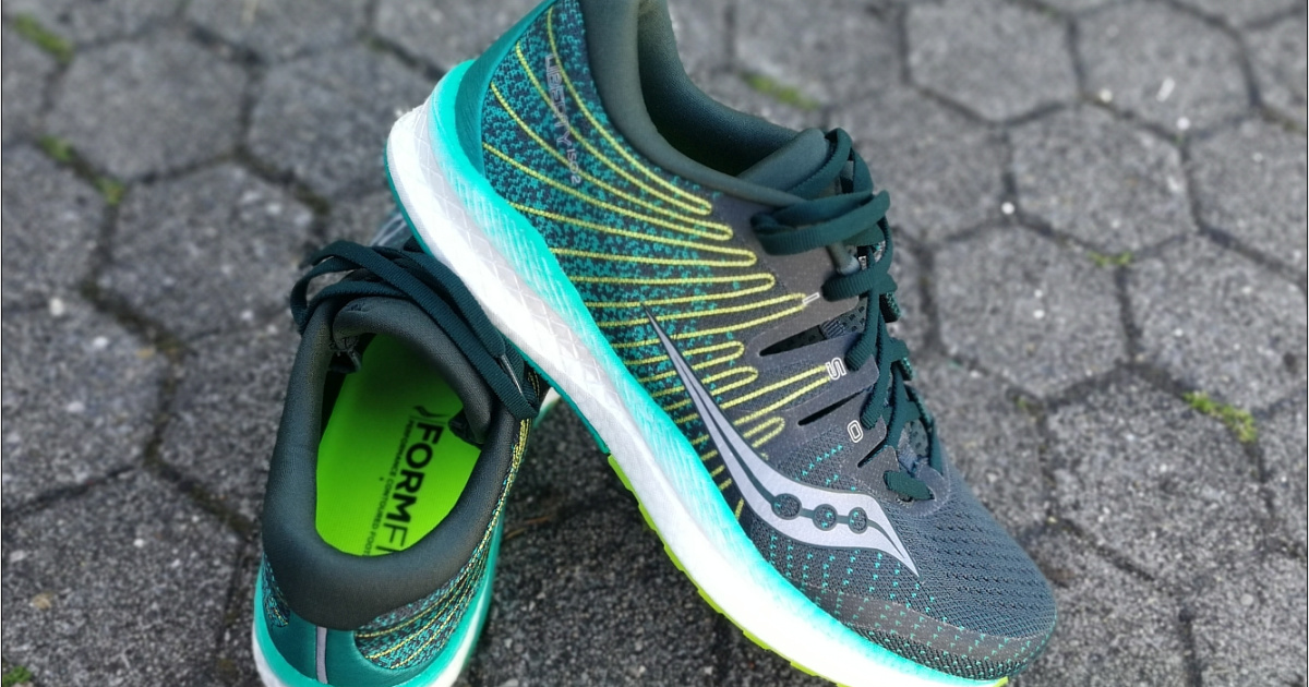 pair of blue green mens running shoes stacked on each other on the asphalt