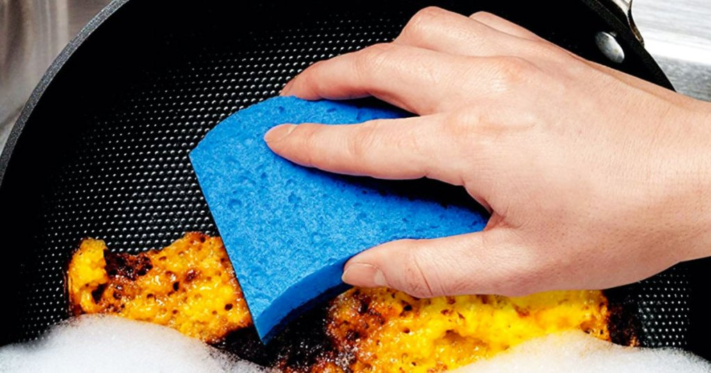 person using a blue sponge on a frying pan
