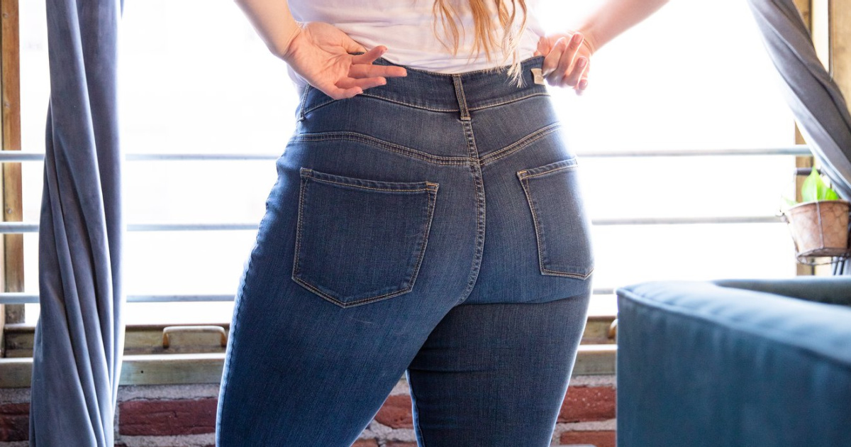 Woman putting on high rise denim jeans