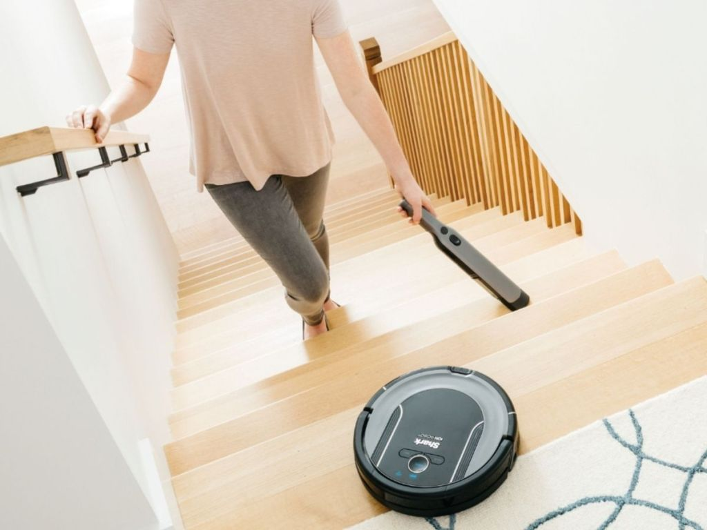 Shark Ion Robot Cleaning System at the top of a stairway with woman using the handheld attachment