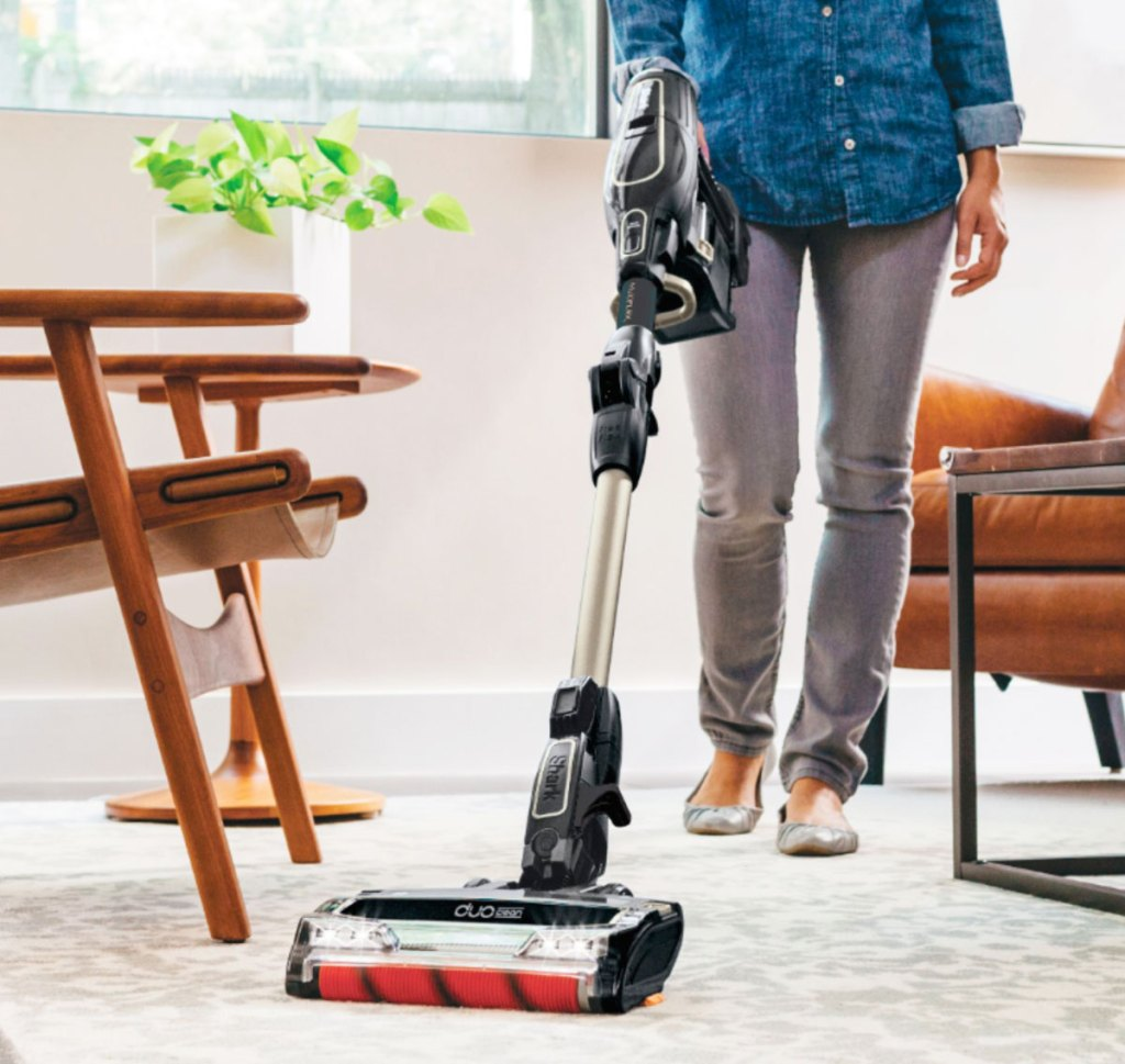 woman using a cordless vacuum on carpet