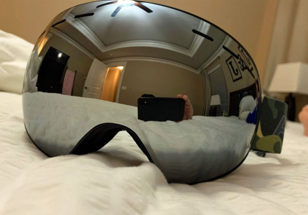 pair of black mirrored ski goggles on a bed