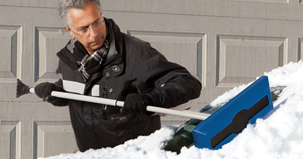 man using Snow Joe Window Scraper on snowy windshield