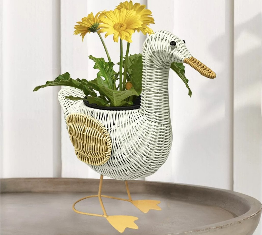 duck planter with a flower in it