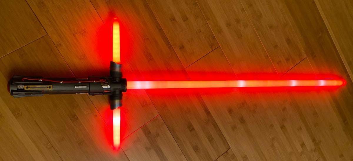 red lightsaber lit up and laying on a wooden floor