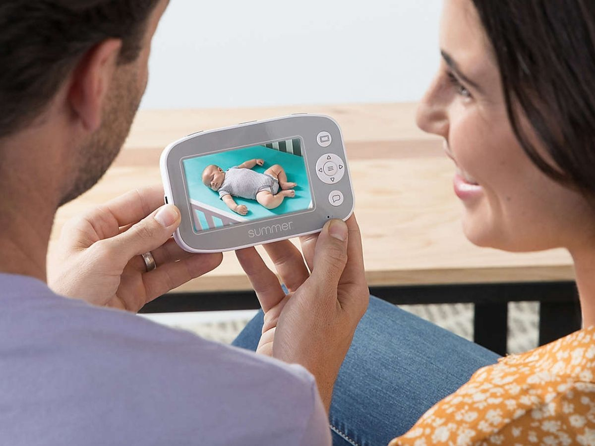 Couple looking at baby on video baby monitor