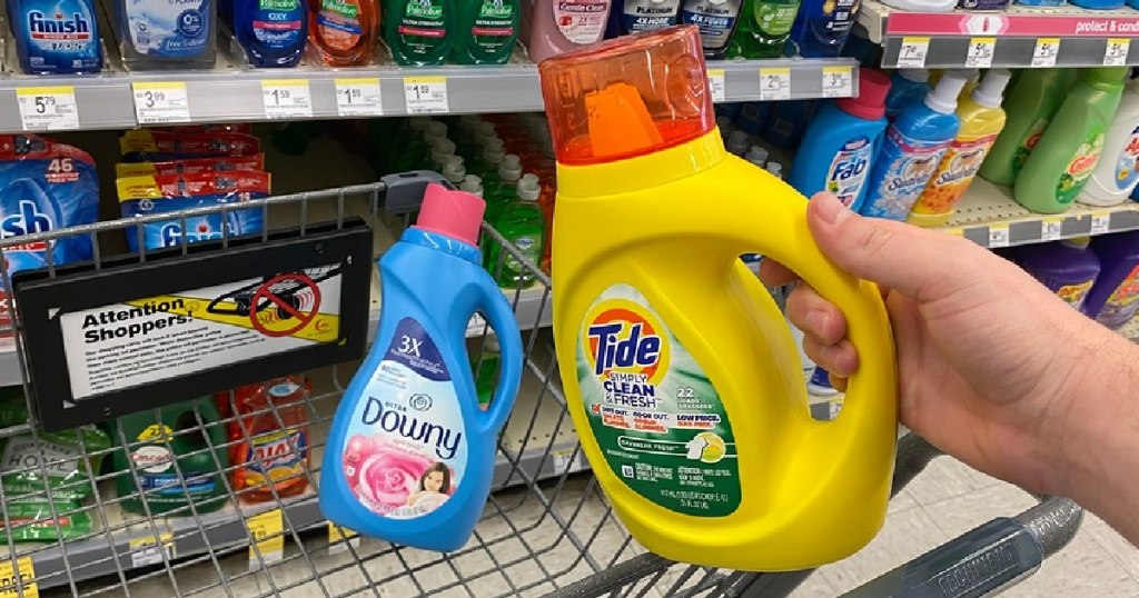 hand holding up a bottle of tide detergent in front of a cart with downy fabric softener in store