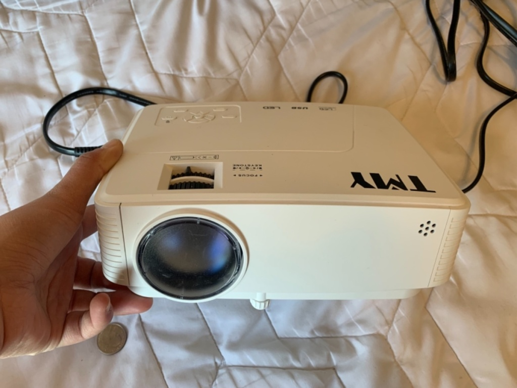 holding white movie projector