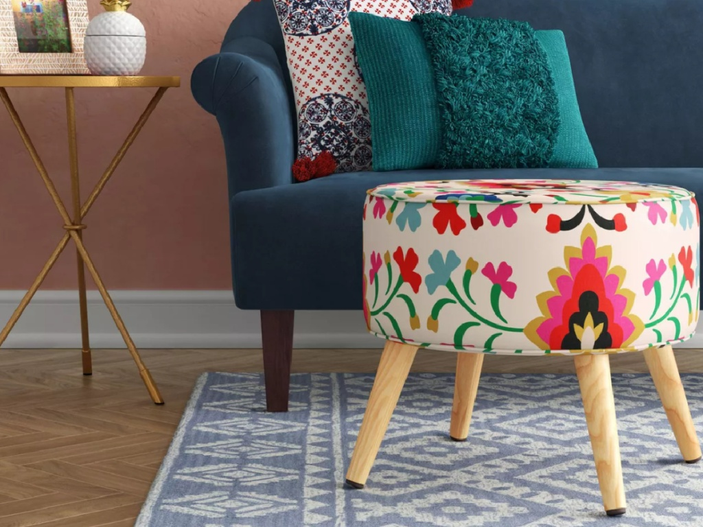 colorful floral footrest in front of a teal couch