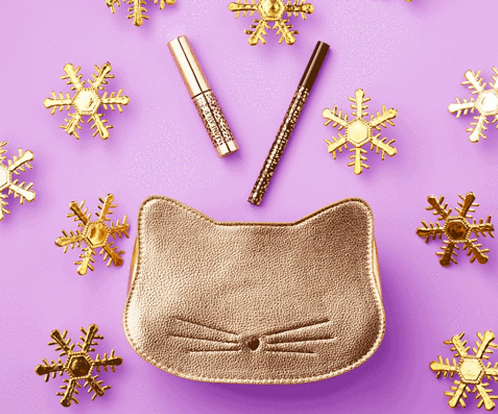 metallic gold cat head shaped makeup bag with eyeliner and mini mascara coming out of it