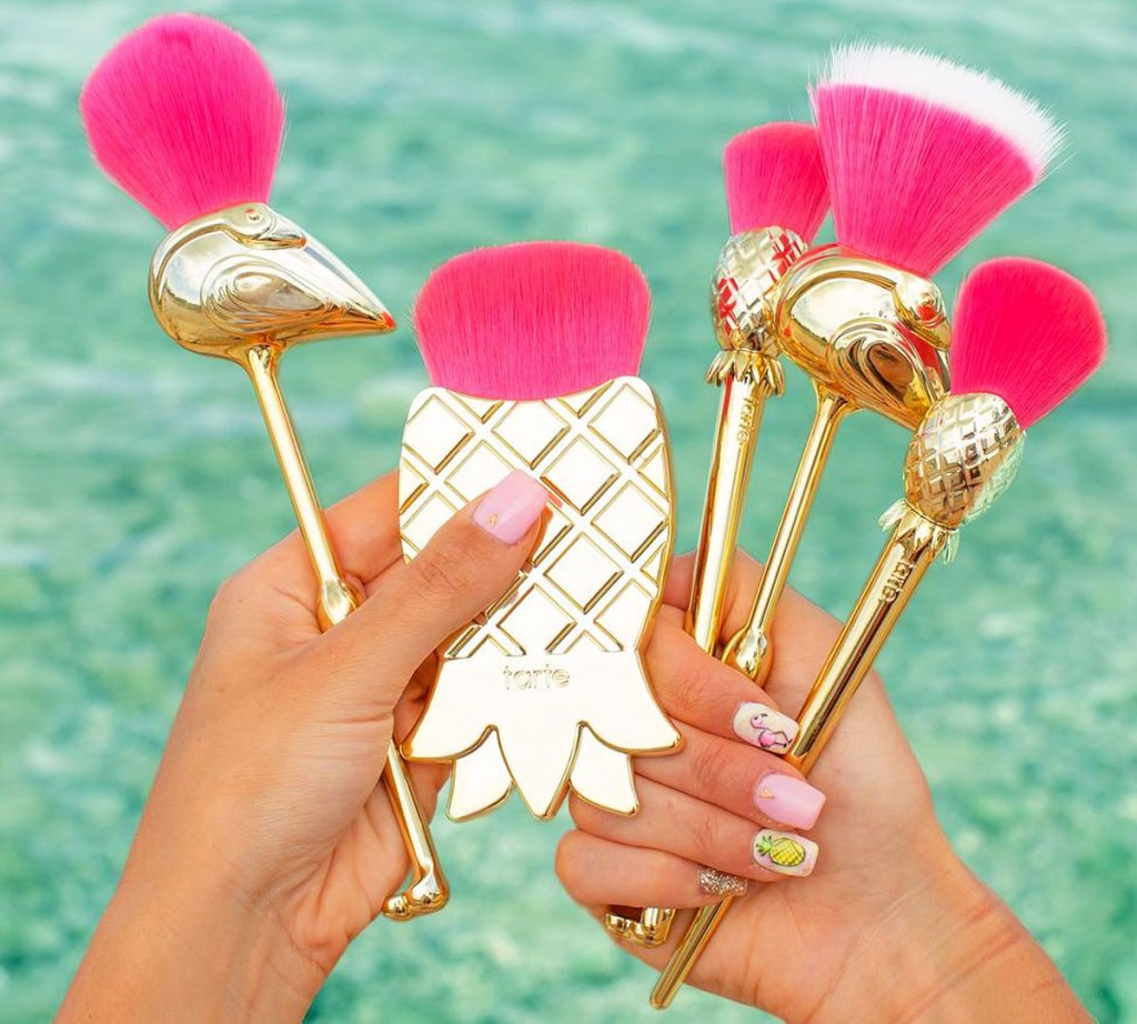 woman holding gold and pink set of flamingo and pineapple shaped makeup brushes