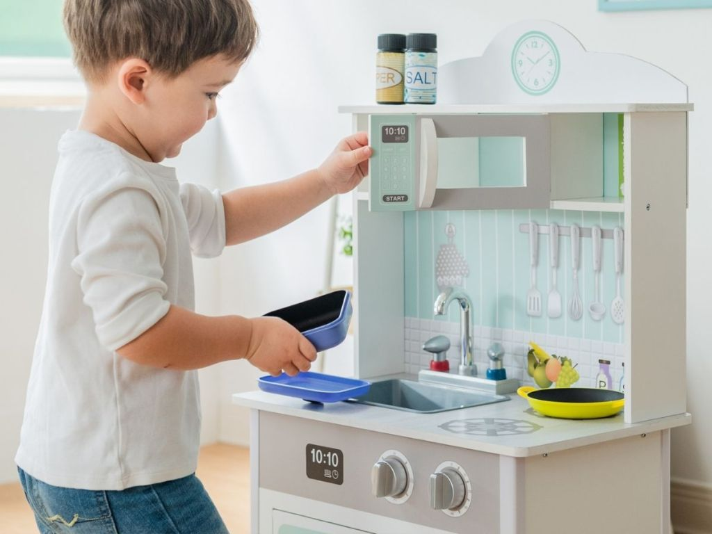 boy playing with kitchen playset