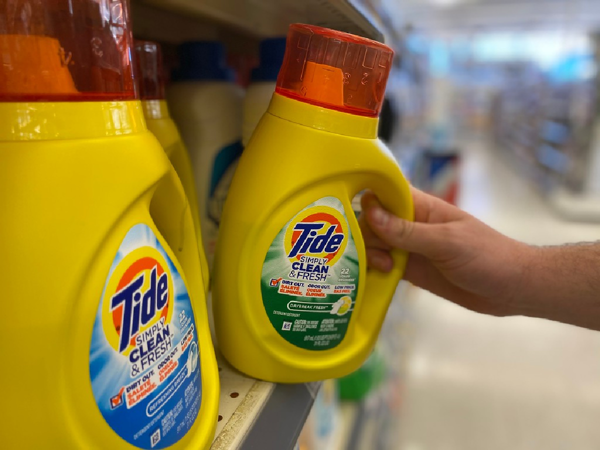 hand tipping a bottle of tide detergent off the edge of a store shelf