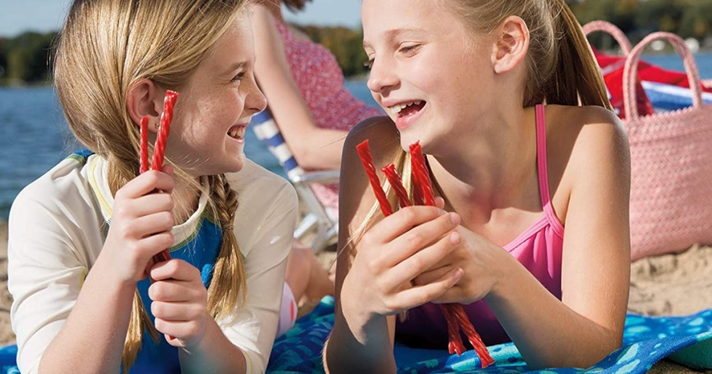 girls on a beach eating Twizzlers