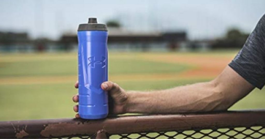 person holding blue Under Armour Squeezable Water Bottle on fence