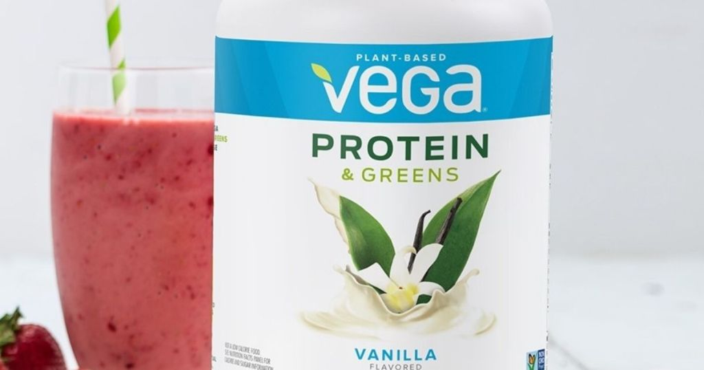 Vega Protein and Greens powder container next to a smoothie
